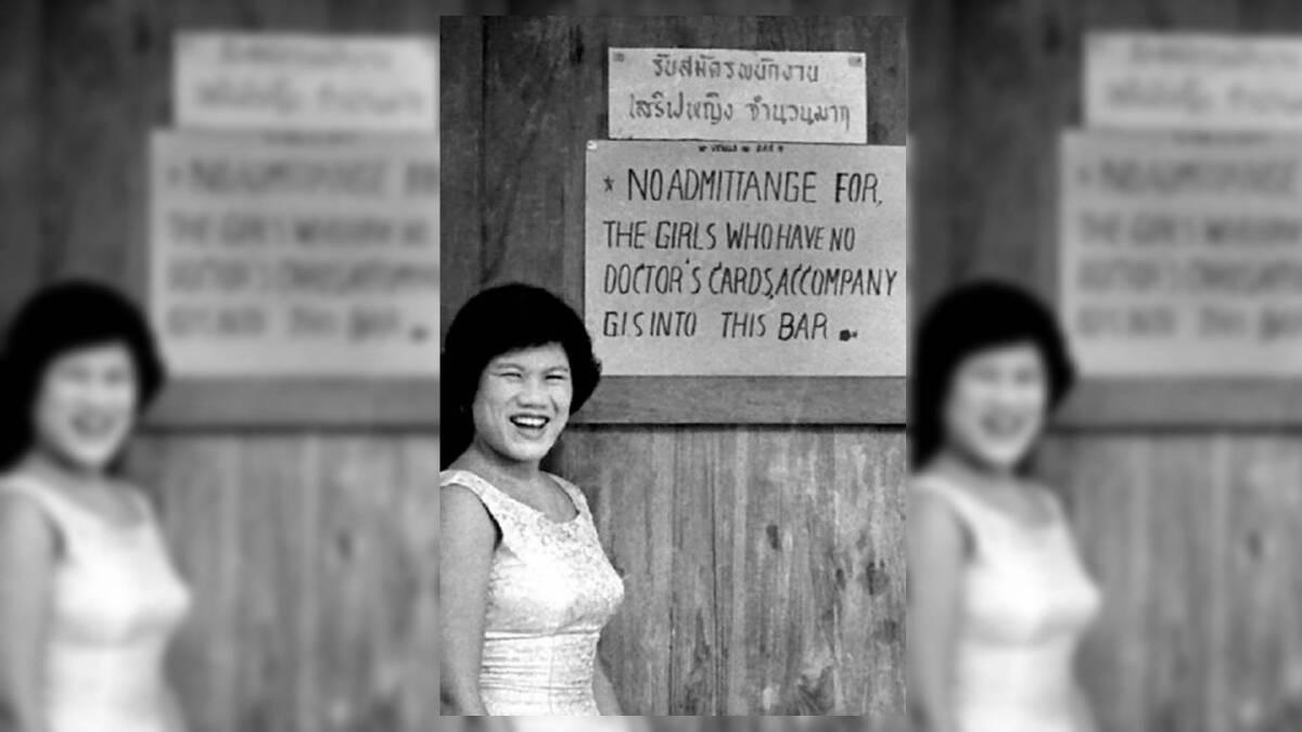 ภาพหญิงสาวหน้าป้ายภาษาอังกฤษที่บอกว่า ห้ามผู้หญิงที่ไม่มีบัตรตรวจโรค เข้ามาในบาร์ หรือแม้จะมากับทหาร จี.ไอ ก็ตาม
