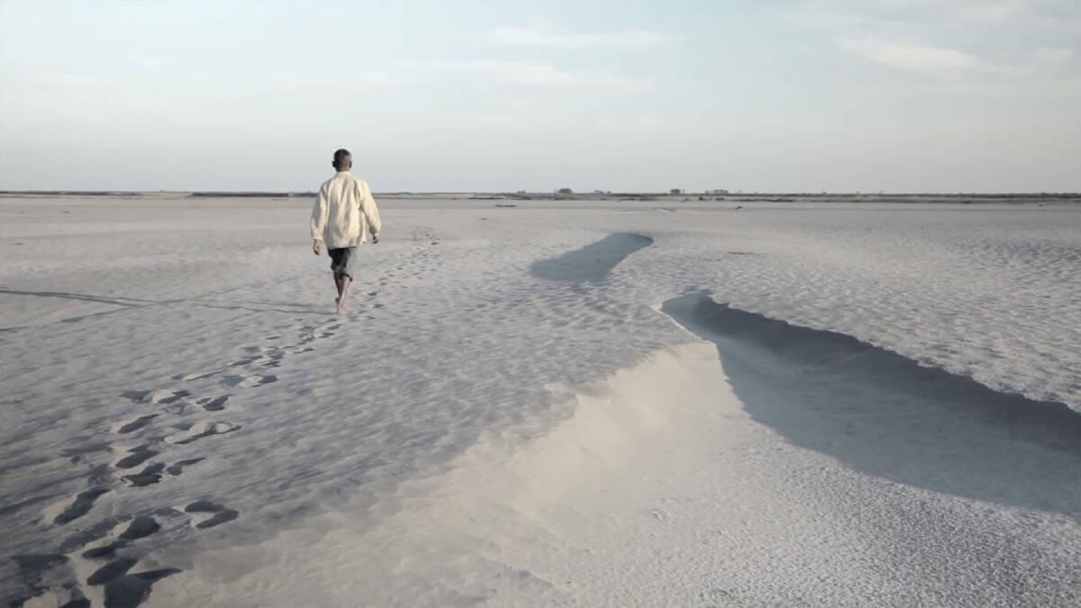 จาดาฟ ปาเยง กำลังเดินบนผืนทรายที่ว่างเปล่าบนเกาะมาจูลี